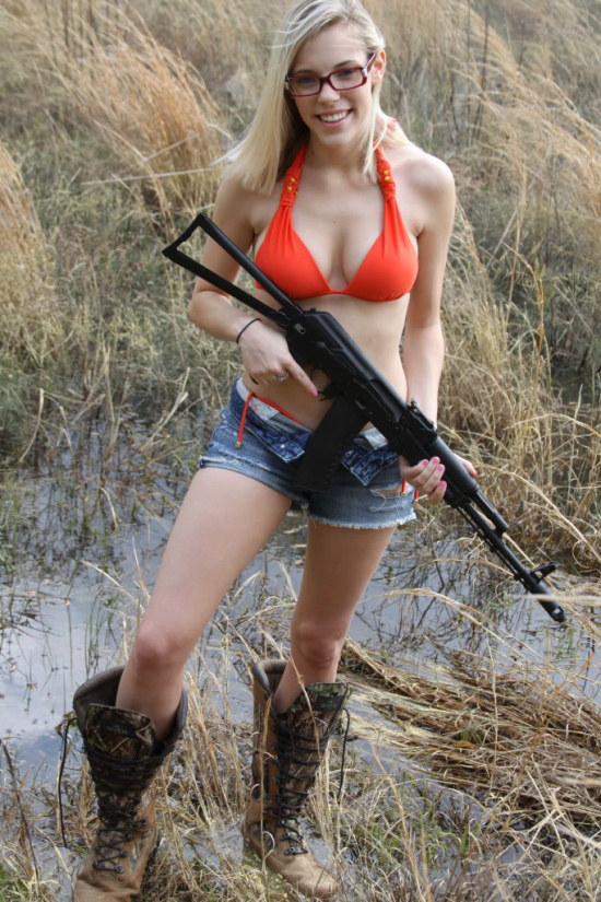 Blonde with a gun in mud boots