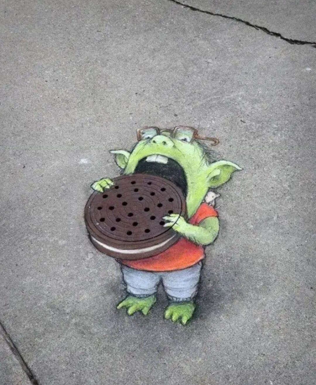Manhole street art eating oreo cookie